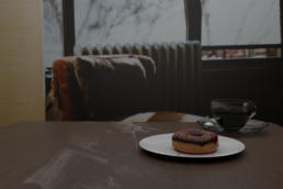 Donut with a coffee on a table Bad Lighting